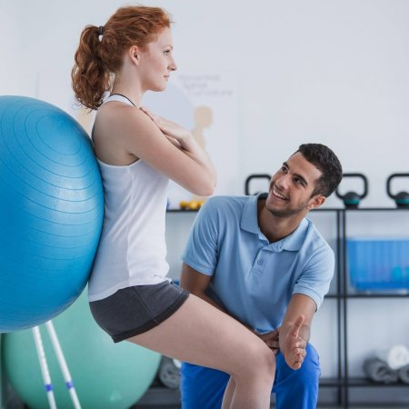 Smiling professional personal trainer helping sportswoman exerci